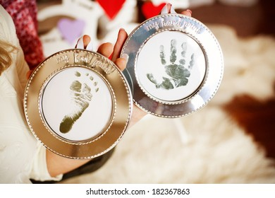 man and woman nahds with pictures of child footsteps