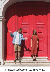 Man and woman near old historical door of european city.