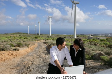 Man and woman next to wind turbines with a laptop computer