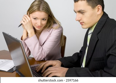 Man and woman at the office desk. There's laptop and notepad on it. Man's typing. Woman's looking at the screen.