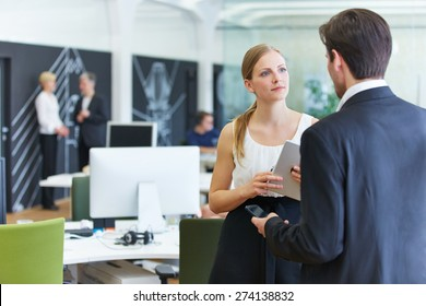 Man and woman in office talking to each other in a break