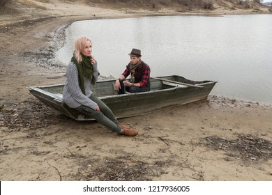 Man and woman in old boat on river coast. Maybe romantic date, or fishers. Man looks old fashioned retro style: hat, smoking pipe, vest, scarf and red plaid shirt looks on pocket watch. HDR image