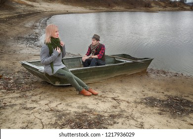 Man and woman in old boat on river coast. Maybe romantic date, or fishers. Man looks old fashioned retro style: hat, smoking pipe, vest, scarf and red plaid shirt. HDR image