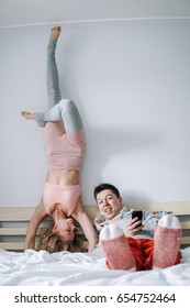 man and woman on the bed, girl standing on hands upside down