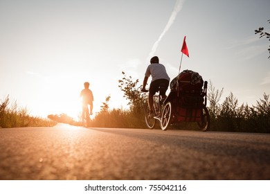 Man and woman are on the bikes on the road trip with the baby coach. Strong warm sunset light. Wide view from below. Back side shot.