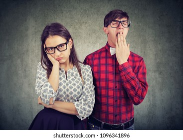 Man and woman on date both looking dull and disinterested standing on gray backdrop.