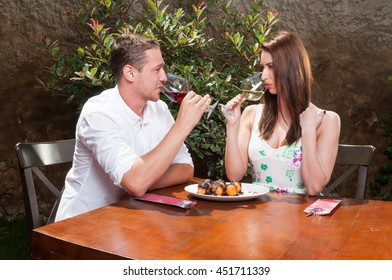Man and woman on date drinking wine on terrace outside and having desert