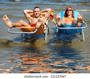 Man and woman on the deck-chair to the beach