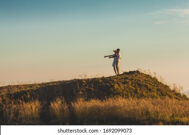 Man and woman on a hill with straightened hands