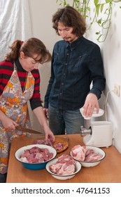 The man and the woman on kitchen prepare a mincemeat.