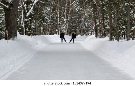 A man and a woman on a liesurely skate on the forest trail through Arrowhead Park in Ontario