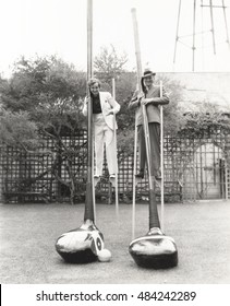 Man and woman on stilts holding giant golf clubs