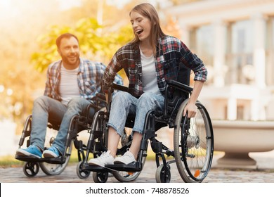 A man and a woman on wheelchairs ride around the park. They arranged a race in wheelchairs. On a background of a beautiful green park.