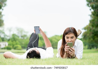 Man and woman on white shirt lie down on grass in public park use smartphone and ear phone together, technology conceptual