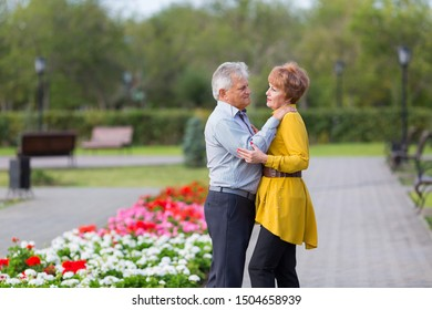 Man and woman pensioners gently hug each other a city park. Loving seniors in the park.