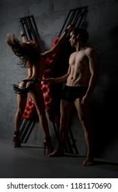 Man and woman perfoming erotic bdsm play shot