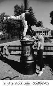 man and woman performing acrobatic tricks on the street