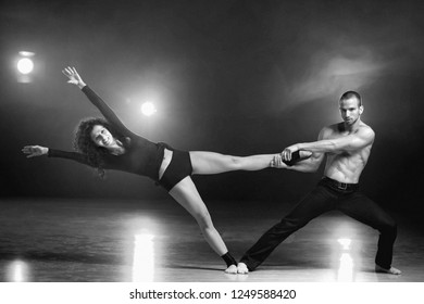 A man and a woman performing a contemporary dance pose on a stage.