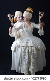 a man and a woman in period costume and wigs and holding a theatrical mask