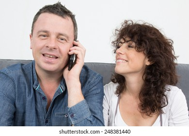 Man and woman with a phone at home