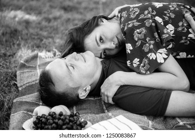 Man and woman picnicking in the park on the lawn