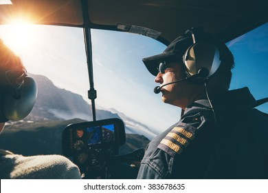Man and woman pilots flying a helicopter on a sunny day. Inside shot of a helicopter.