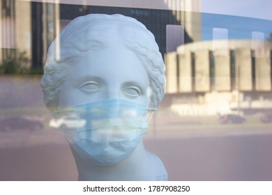 a man, woman plaster bust in a protective medical mask behind a plate-glass window with reflection of city streets