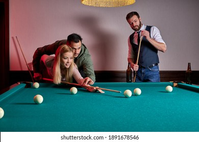 man and woman are playing billiards, a guy is teaching a female to play billiards. entertainment, holiday concept