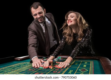 Man and woman playing at roulette table in casino
