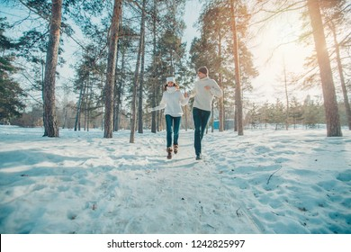 man and woman playing in the snow. Couple in love in the winter forest