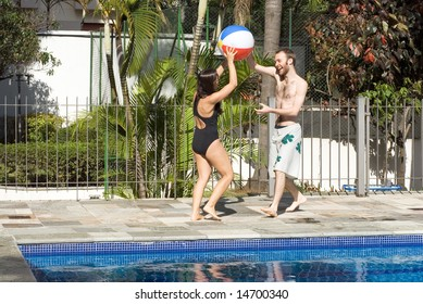 A man and a woman are playing together next to a pool.  They are smiling and laughing and looking at each other.  They are holding a beachball.  Horizontally framed photo.