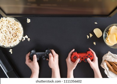 Man and woman playing video games together, top view of gamer accessorises and snacks frame, flat lay on black background. Joystick and gamepad, keyboard, game console, beer, chips and popcorn.