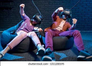 Man and woman playing in virtual reality simulating car driving using VR headsets in the playing room