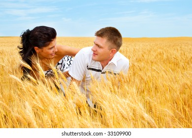 A man and woman playing in the wheat field
