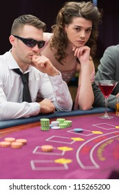 Man and woman at poker table in casino