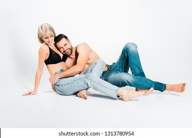man and woman posing in underwear and jeans on grey