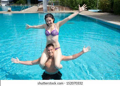 Man and woman posing in the water at public swimming pool. She is sitting on his shoulder