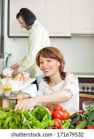 A man and a woman with a positive vegetables in the kitchen of his home