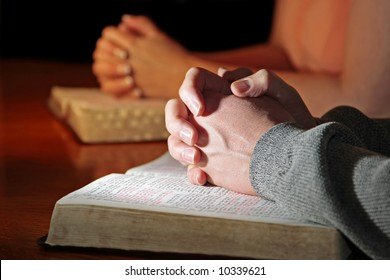 A man and woman praying together with their Bibles - male foreground hands highlighted (Christian image, shallow focus).