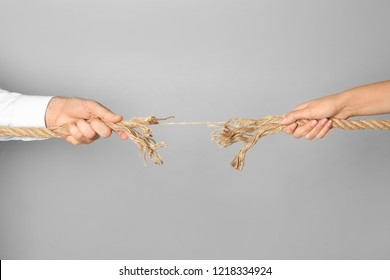 Man and woman pulling frayed rope at breaking point on gray background