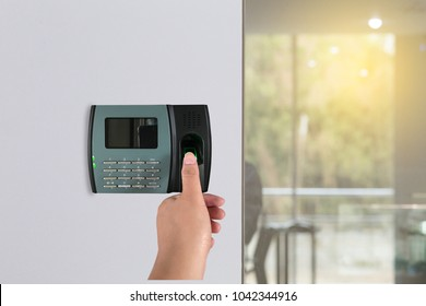 Man or woman push finger down on finger scan machine for access door security systems. Close up and selective focus