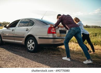 Man and woman pushing a broken car, back view