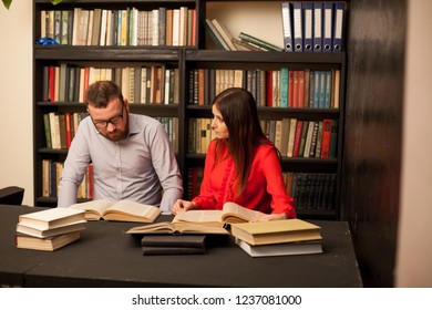 a man and a woman read books in the library are preparing for the exam