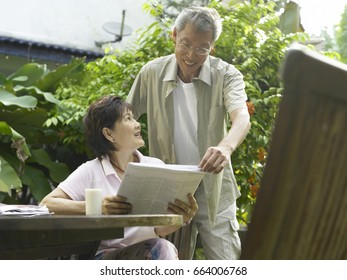 Man and woman reading newspaper in the garden