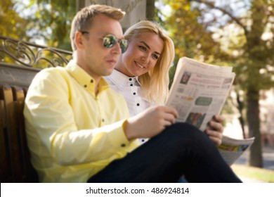 Man and woman reading newspaper on a bench. Warm autumn and sunny day in the park.