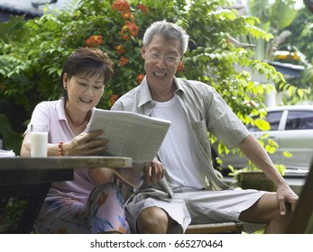 Man and woman reading newspaper in their garden