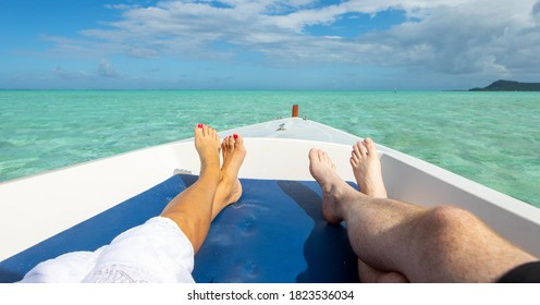 Man and woman relaxing as couple on the bow of a boat over beaut