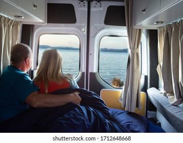 Mann und Frau entspannen sich im Wohnwagen und beobachten am See. Freier Reisebegriff.