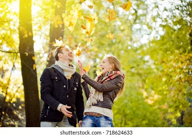 Man and woman relaxing on the autumn park, throwing yellow maple leaves