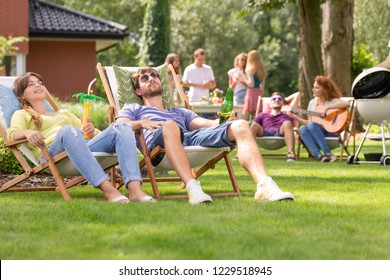 Man and woman relaxing on sunbeds during grill party with friends in the garden